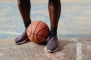 A basketball between a man's legs.