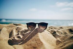 A pair of sunglasses on a beach in summer.