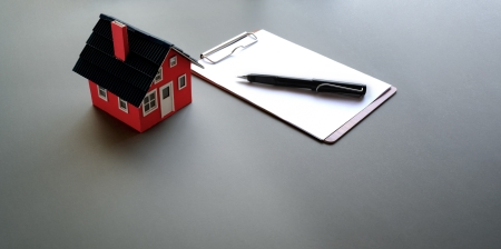 A model house with pen and paper near it.