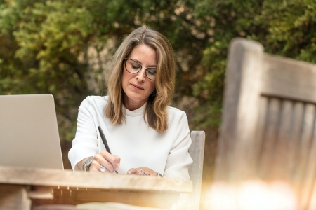 A white woman writing on a table.