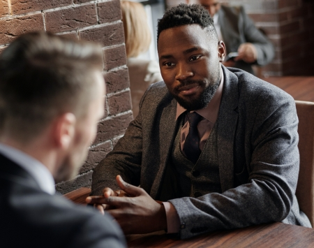 An African-American man and a white man at a table in a meeting.