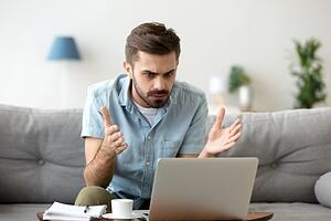 A man frustrated on his computer.