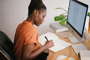 A person writing with a computer in front of her.