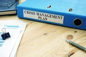 A folder containing a crisis communications plan.