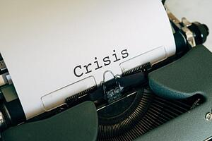 "A typewriter with paper and the word ""crisis"" is written on it."