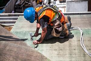 A man hammering down a nail in a construction site.