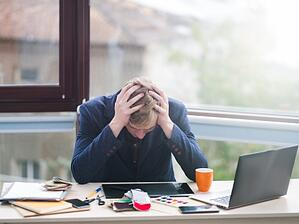 A frustrated man in a crisis near a computer.