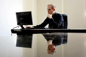 A man in front of a computer, thinking.