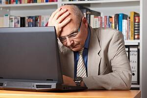 A frustrated businessman in front of a computer.