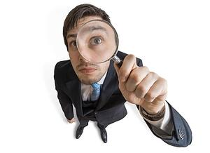 A man monitoring something with a magnifying glass.